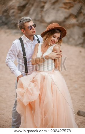 Bride In Long Dress And Groom In Sunglasses Stand And Smile In Canyon Against Background Of Rocks. C
