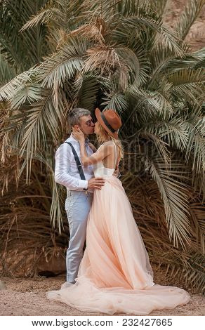 Bride In Long Dress And Groom In Sunglasses Stand, Hug And Kiss On Background Of Palm Trees.
