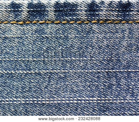 Background Of Denim Fabric With Seam. Blue Jeans Cloth Stitching With Orange Thread. Old Vintage Bac