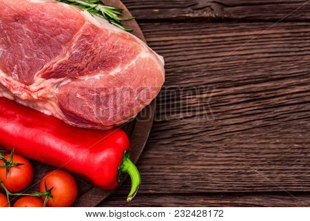 Close Up Raw Pork Steak On Wooden Cutting Board With Red Chili Pepper, Peppercorn, Garlic, Tomatoes