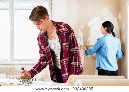 Young man applying adhesive to the back of the wallpaper sheet while his girlfriend is measuring the prepared wall in their new home