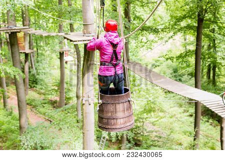 Woman sliding in barrel at high rope climbing course outdoors