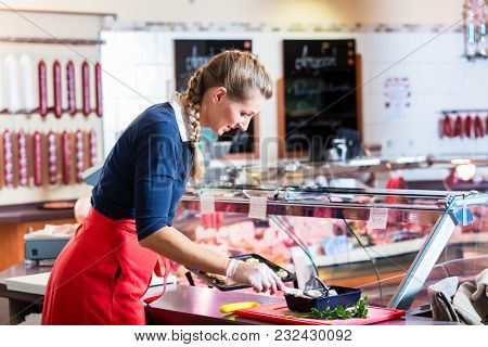 Butcher woman cutting piece of rib meat in her shop with a knife