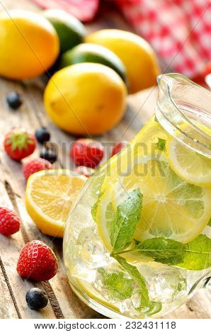 Fresh Lemon-lime Water With Mint And Ice In A Glass Pitcher And Strawberries, Blueberries And Lemons