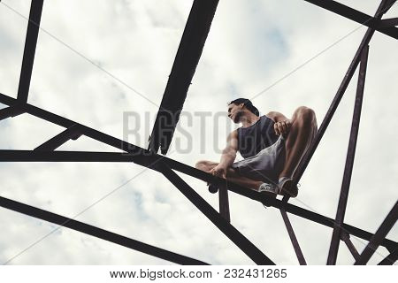 Young Risky Guy Balancing And Sitting On The Top Of High Metal Construction, Outdoors