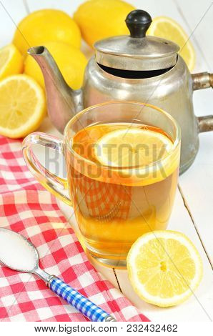 Black Tea With Slice Of Lemon In Glass Mug, Old Teapot, Teaspoon Of Sugar, Red Checkered Tablecloth