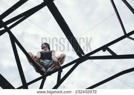 Young Guy Balancing And Sitting On High Metal Construction, Outdoors