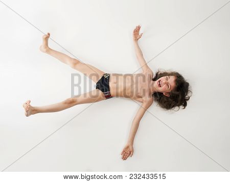 Long-haired Little Boy In A Swimsuit Lying On His Back, Isolated On A Light