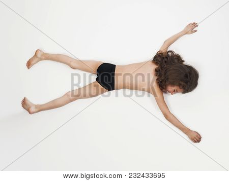 Adorable Little Boy In Bathing Suit Lying On Stomach With Arms Outstretched, Isolated On Light