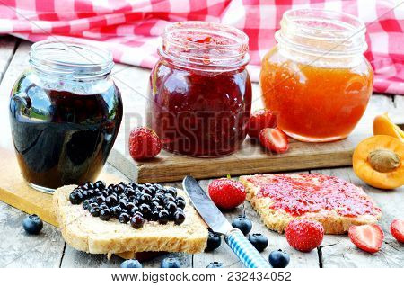 Three Jars Of Fruit Jam - Blueberry, Strawberry, Apricot, Spilled Blueberries, Knife And Toast Bread