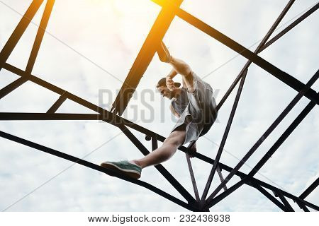 Young Brave Man On The Top Of High Metal Construction, Outdoors