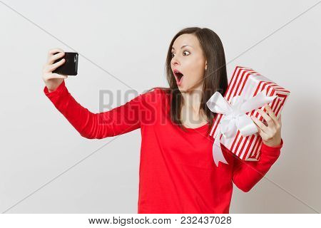 Woman Doing Selfie On Mobile Phone With Red Striped Present Box With Gift Isolated On White Backgrou