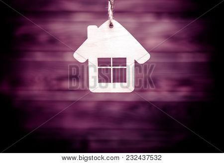 The Symbol Of The House Stands On A Brown Wooden Background