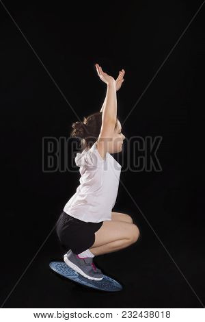 Little Caucasian Girl Doing Squats On Balance Board. Photo On Black Background