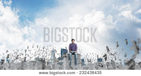 Young Man In Casual Clothing Sitting Among Flying Letters With Cloudly Skyscape On Background. Mixed