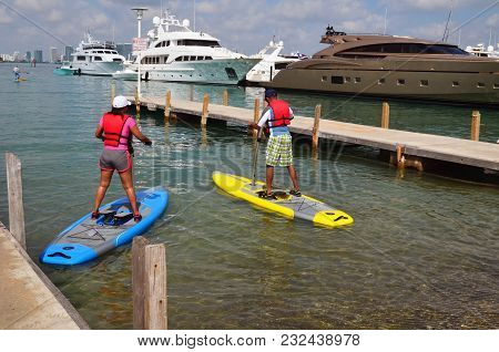 Young Couple Trying Out Pedal Boards The Latest Addition To The Paddle Board Fad.