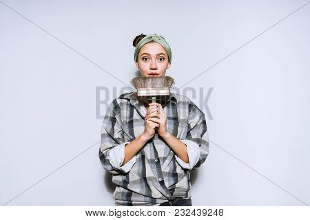 Cute Young Girl In A Plaid Shirt Holding A Paintbrush For Painting The Walls, Doing Repairs In Her N