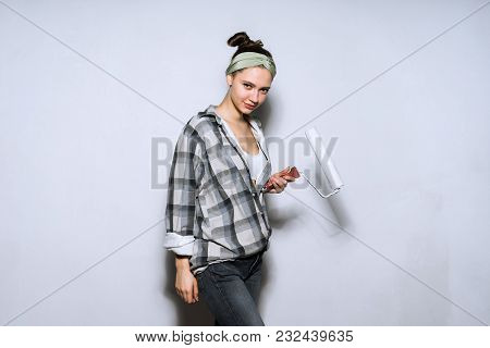 Beautiful Young Girl In Plaid Shirt Colors The Wall With A Platen In White Color, Doing Repairs