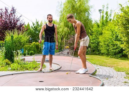 Couple, man and woman, playing miniature golf together outdoors