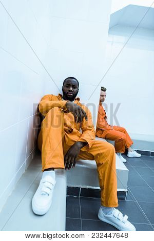 Multicultural Prisoners Sitting On Benches In Prison Cell