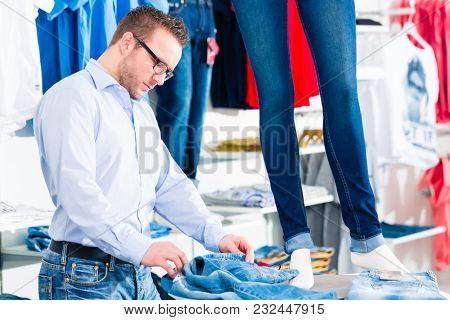 Handsome Man buying blue jeans in fashion shop or store