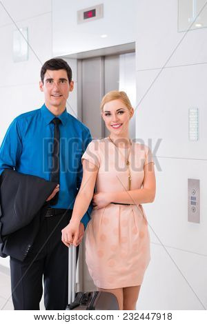 Happy couple waiting for hotel elevator or lift