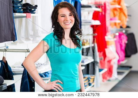 Woman buying fashion blue jeans in fashion shop or store