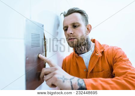 Tattooed Prisoner In Orange Uniform Pressing Button In Prison Cell