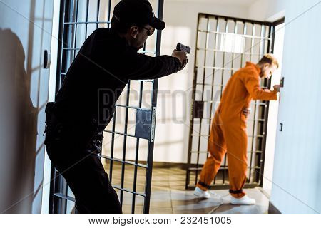 Prison Guard Aiming Gun At Escaping Prisoner