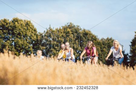 Family riding their bikes shot above a grain field in summer