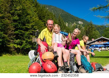 Happy family having break from hiking in the mountains