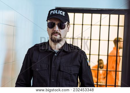 Prison Guard Standing Near Prison Cell With Multicultural Inmates