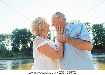 Low-angle side view portrait of a romantic senior couple in love enjoying a healthy and active lifestyle outdoors in summer