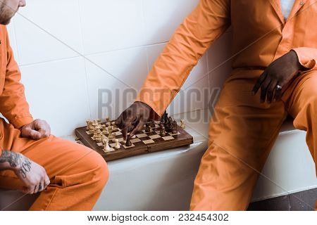 Cropped Image Of Multicultural Prisoners Playing Chess In Prison Cell