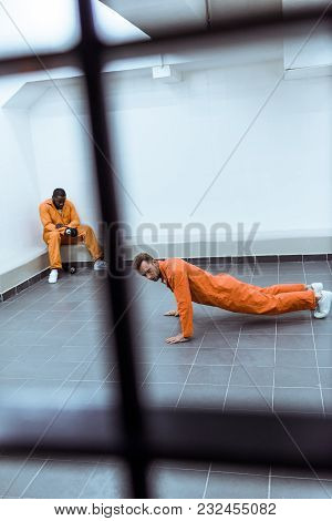 View Of Prisoner Doing Push-ups In Prison Cell