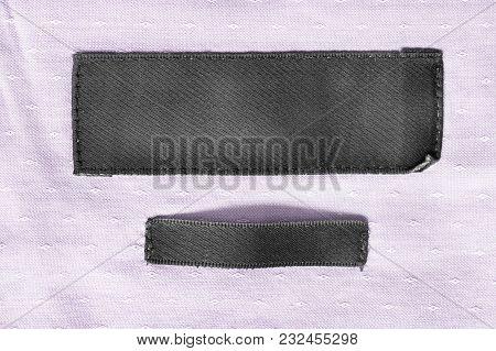 Black Blank Textile Clothes Label On Pink Cotton Background Closeup