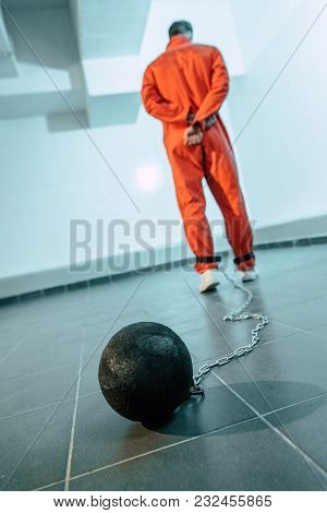Rear View Of Prisoner In Orange Uniform With Weight Tethered To Leg