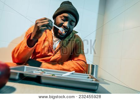 African American Convict Eating In Prison Cell