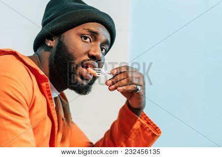 African American Prisoner Eating In Prison Cell