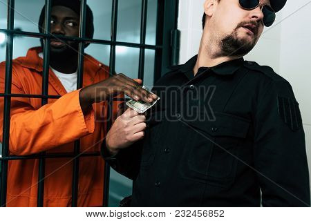African American Prisoner Giving Money To Prison Warden As Bribe