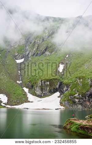 Mighty Mountains Are Covered With Fog And The Lake At The Foot, Transylvania, Romania. Small Figure