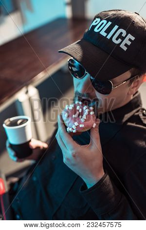 High Angle View Of Prison Guard Eating Doughnut And Holding Cup Of Coffee