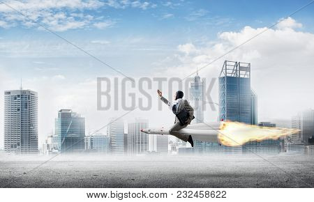 Conceptual Image Of Young Businessman In Suit Flying On Rocket Above Asphalt Road With Cityscape And