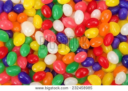 Many Brightly Colored Jelly Beans In A Rainbow Of Colors. Popular Candy For Easter. Wooden Spoon On
