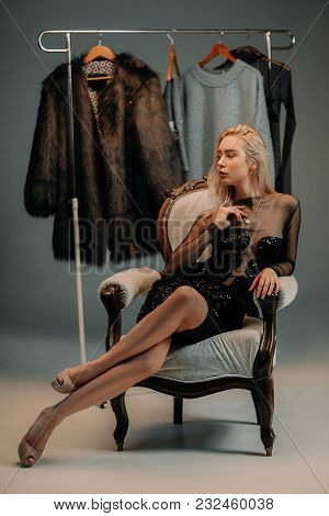 Young Woman In Black Dress Sits In Armchair Next To Rack With Hangers And Clothes.