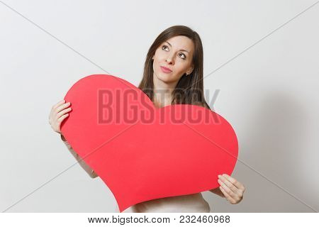 Beautiful Young Pensive Woman Holding Big Red Heart In Hands Isolated On White Background. Copy Spac