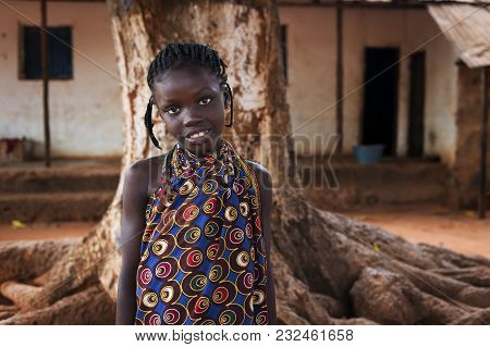 Nhacra, Republic Of Guinea-bissau - January 28, 2018: Portrait Of A Young African Girl In Front Of H