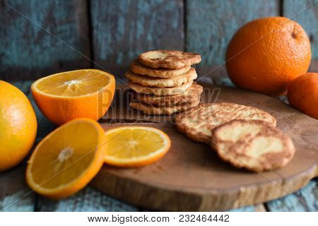 Healthy Sweets. Pile Of Homemade Vegetarian Cookies And Orange Slices On Wooden Slab On Shabby Blue