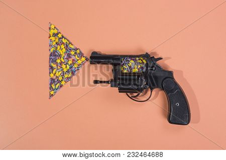 Revolver And Easter Confectionery Powder On A Beige Background