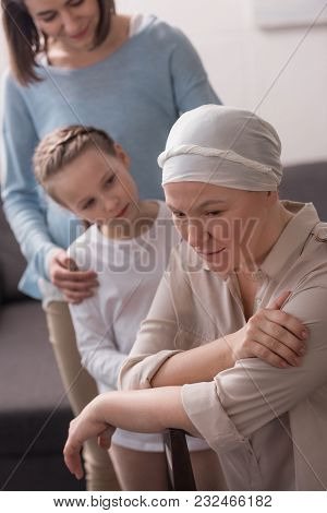Family Supporting Mature Sick Woman In Kerchief
